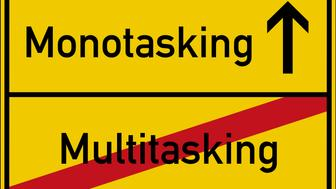 The words multitasking and monotasking on a road sign