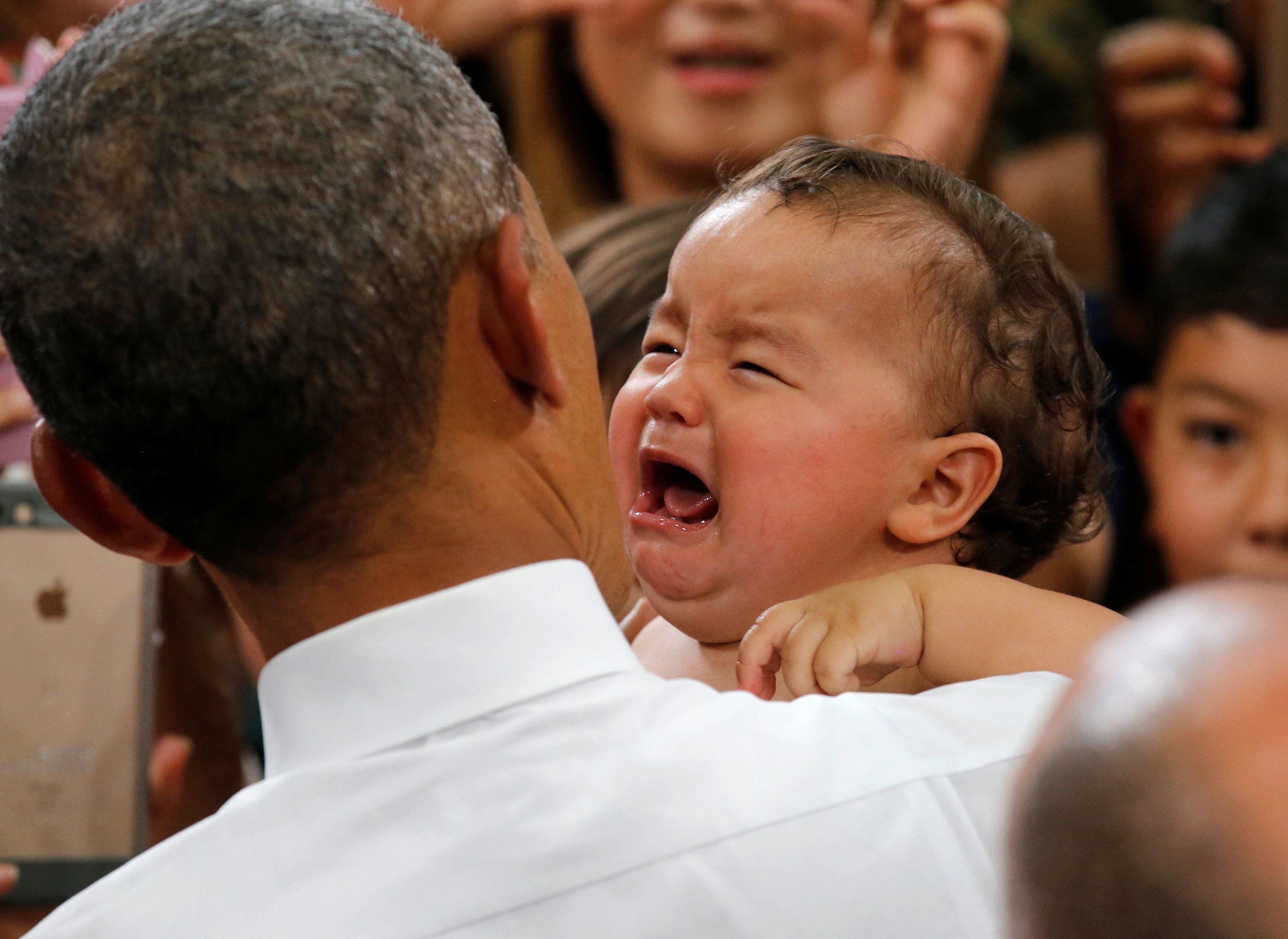 A baby cries as U.S. President Barack Obama holds the baby during his visit at Iwakuni Marine Corps Air Station, enroute to H