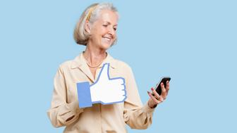 Senior woman with cell phone holding fake like button against blue background