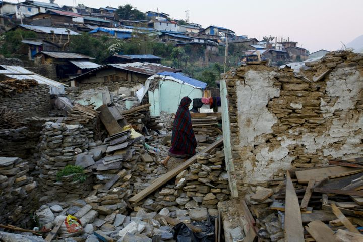 A Nepalese woman still searches her belongings on the debris of her destructed house in Barpak of the Gorkha District, Nepal,