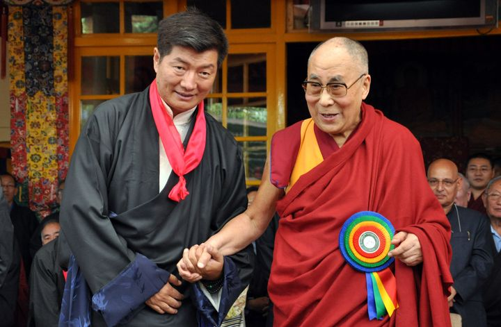 Lobsang Sangay, the prime minister of Tibet's government in exile, stands next to the Dalai Lama as he greets the crowd at hi