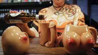 "27-year-old Lu Lu, the owner of Ke'er restaurant (Shell in English), pours a drink into a penis-shaped cup at her restaurant in Beijing, China, May 26, 2016. With drinks served in breast-shaped cups and beers opened with bottle openers shaped like a wooden penis, the father and daughter team behind a Beijing S&M restaurant are encouraging customers to mix food with sex. Owner Lu Lu said business has been good since opening just under a year ago, with young Chinese streaming in to feast on seafood, such as lobster, under the gaze of mannequins wearing bondage gear.  REUTERS/Kim Kyung-Hoon TEMPLATE OUT  SEARCH ""BEIJING SHELL"" FOR THIS STORY. SEARCH ""THE WIDER IMAGE"" FOR ALL STORIES."