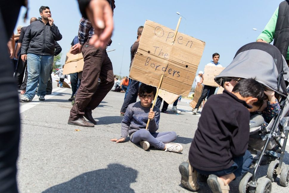 A boy holds a sign on April 4, 2016 on the third day of protest along the highway outside Polykastro, in Central Macedonia, G