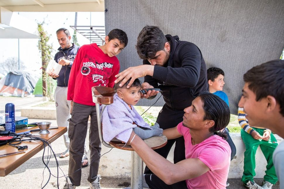 Nine-month-old Ahmad, from Syria, gets a haircut while his 23-year-old father, Farhud, holds his attention. Ali, the barber,
