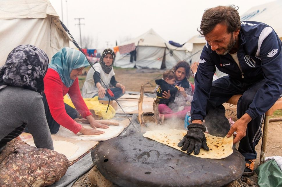 A Syrian family prepares bread to sell from their tent. Using a satellite dish to bake the bread, they start at around 10 a.m