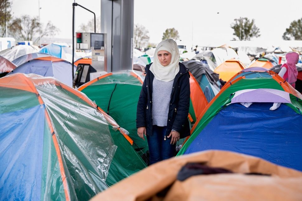 Rahaf Habash, 21, stands next to her small tent near a crowded gas pump. She was married to her husband Basel for fewer than