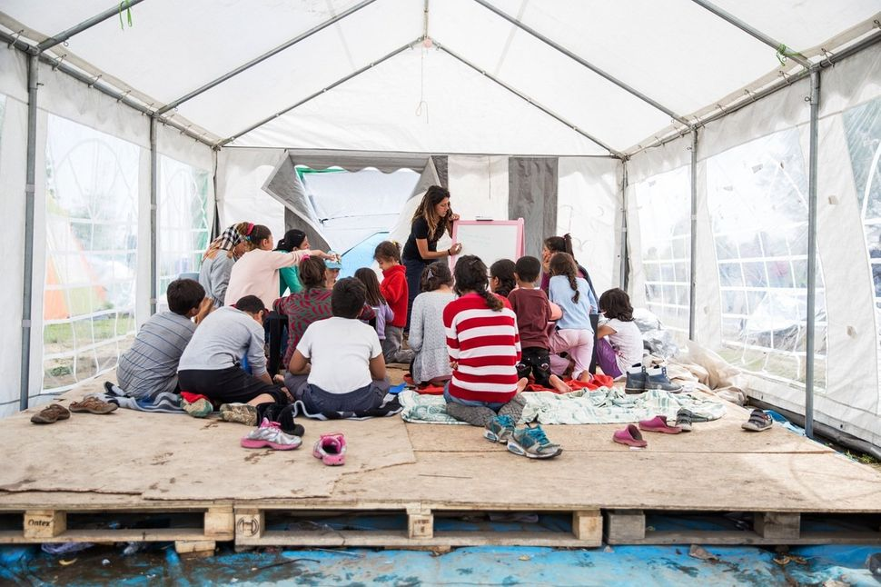 A Palestinian volunteer runs a daily children's English lesson in a donated tent.