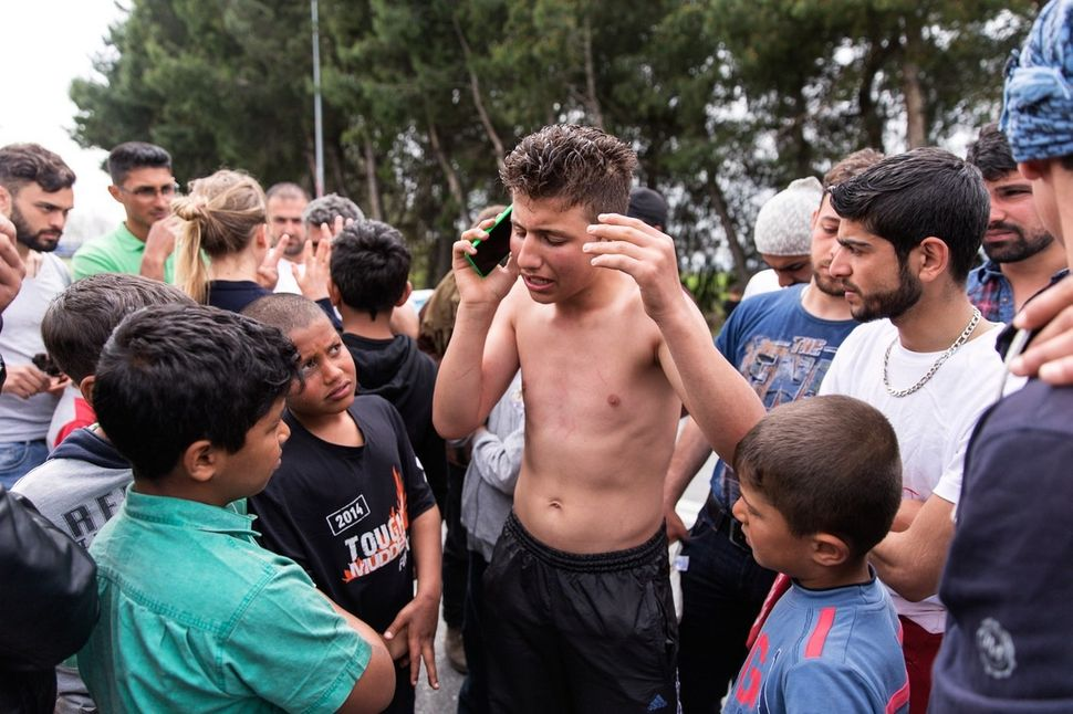 Doused in kerosene, 16-year-old Hesham, an unaccompanied minor, speaks on the phone with a friend after threatening to immola