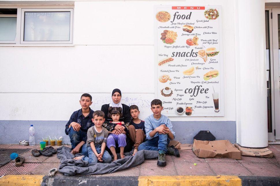 "<i></i>Umm Umran, 41, sits on the pavement with her five children --€"" Umran,16, Mohammed, 15, Ali, 11, Ala'€™a, 6, and Adida"