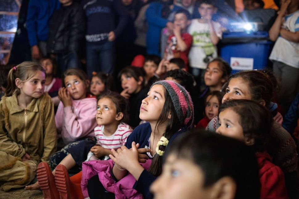Zainab, 12, watches an episode of Mr. Bean at a gathering organized by a Spanish volunteer. Zainab has been living in Idomeni