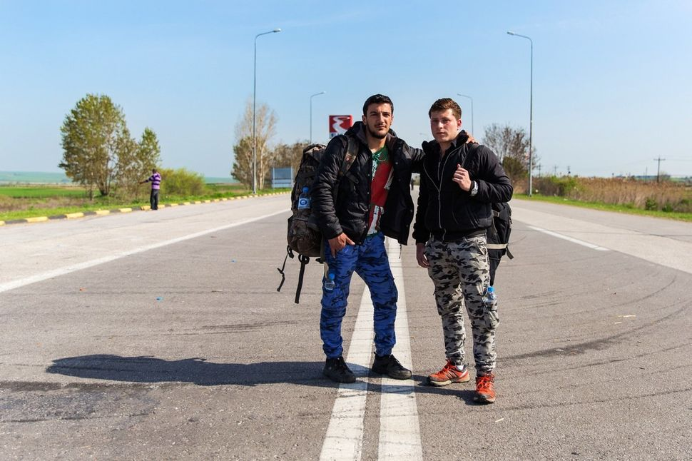 Karam, 19, and Mohammed, 18, both from Hama, Syria, stand in the street with their belongings, preparing to make their way ba