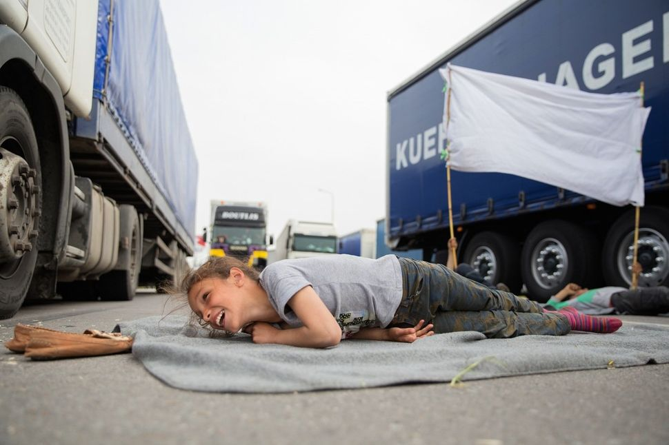 """Heleen, 11, from Qamishli, Syria, lays across the highway in protest against closed borders on April 2, 2016. """"If the border"""