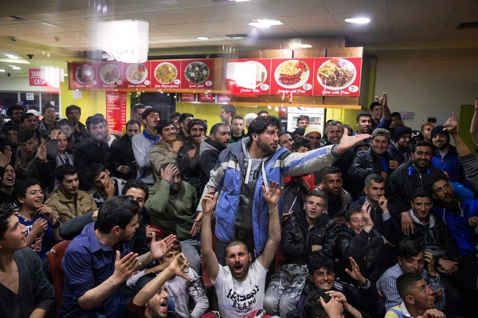 A group of refugees gather on April 2, 2016 to watch a Barcelona vs. Real Madrid soccer game inside the gas station cafe.