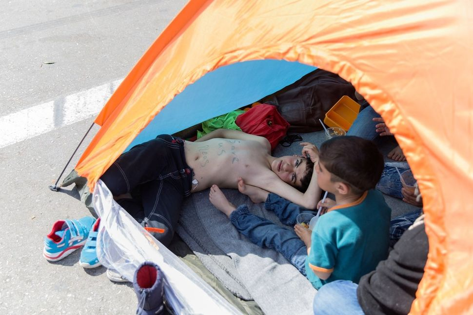 Hadi Al Ishkey, 10, from Damascus, lies in a tent pitched on the highway to protest the border closure between Greece and Mac