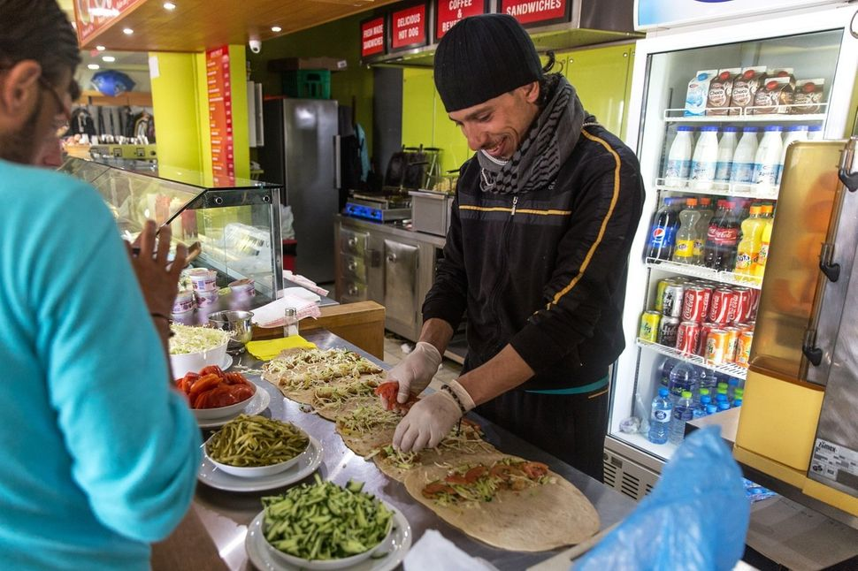 A Syrian prepares falafel in the gas station cafe. The owners allow the former chef to make and sell his street food from the