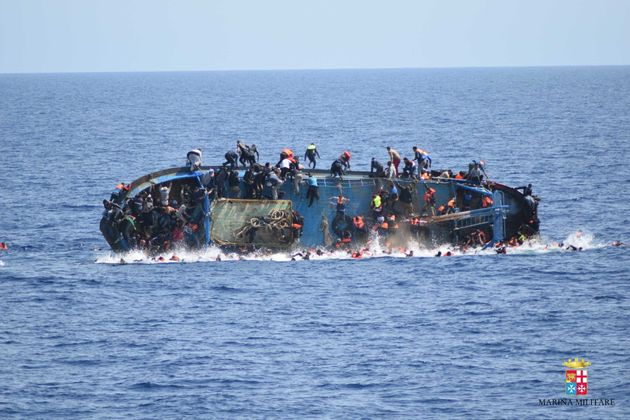An overcrowded migrant boat shortly before capsizing in the Mediterranean Sea between Libya...