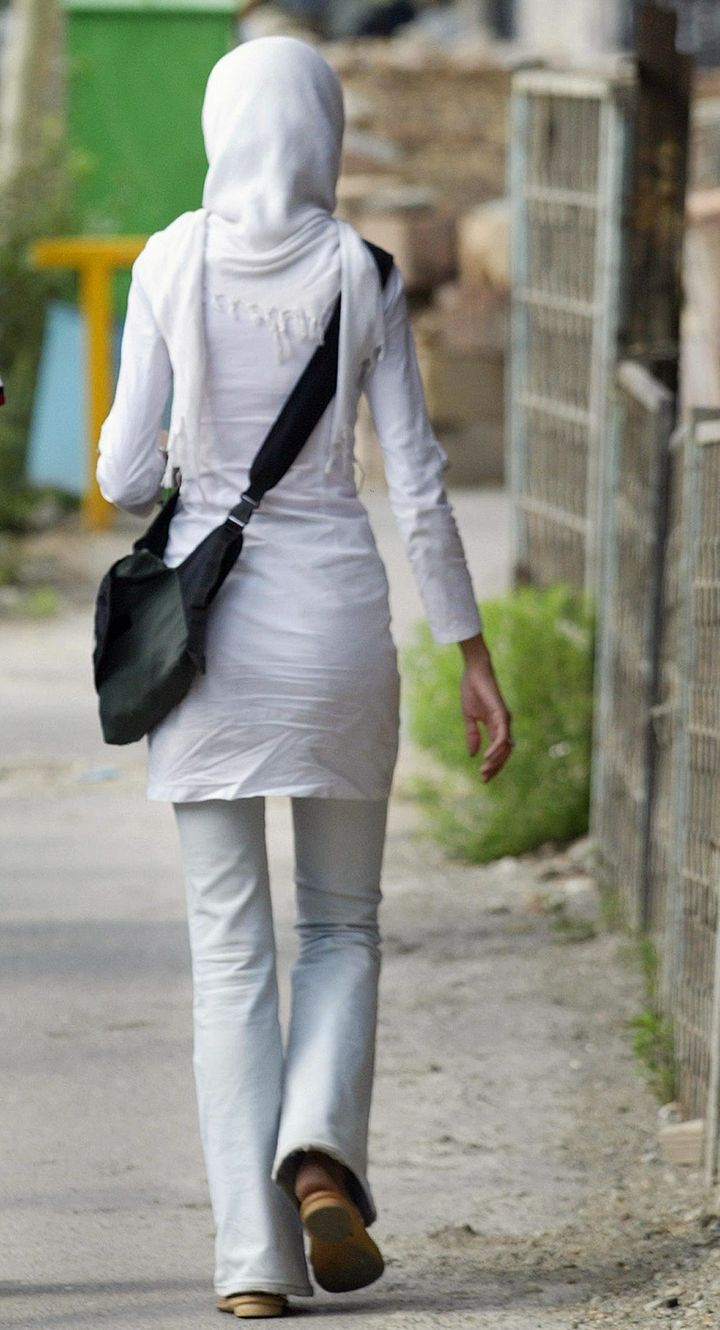 As part of a wider crackdown on behaviors considered to be contrary to Islamic values, authorities punished a group of college students for partying. Here, an unidentified Iranian woman walks on a street in Tehran, on July 13, 2004.