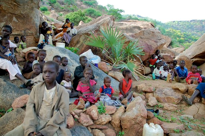 Women and children climb rocky hillsides near Kauda in Sudan's Nuba Mountains to seek cover from government air strikes.&nbsp