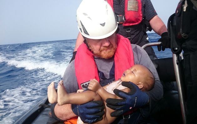 German rescuer from the humanitarian organisation Sea-Watch holds a drowned migrant baby, off the Libyan...