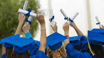 Group of Graduates Dressed in Graduation Gowns Holding Scrolls in the Air
