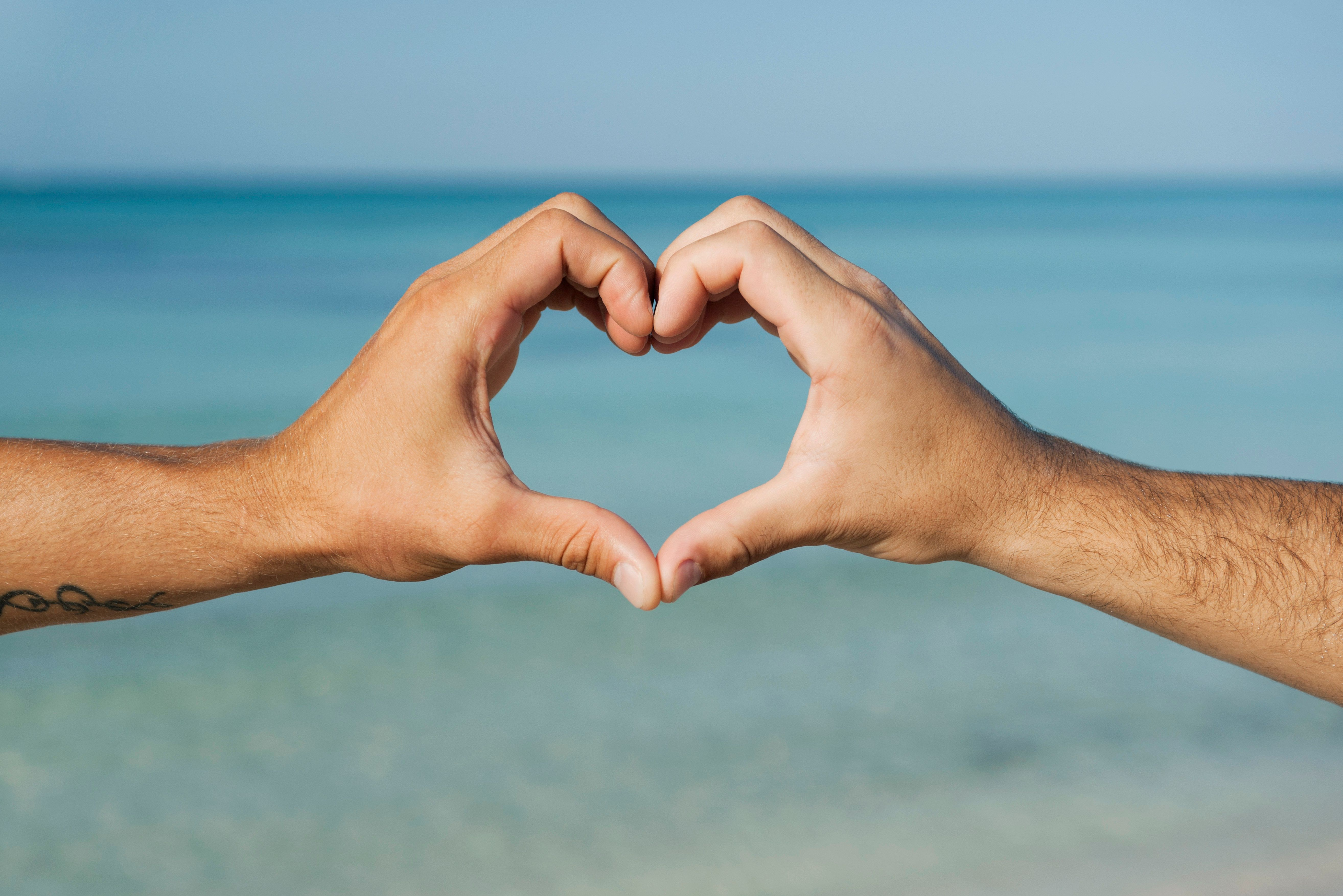 Two men's hands forming heart shape by ocean, cropped