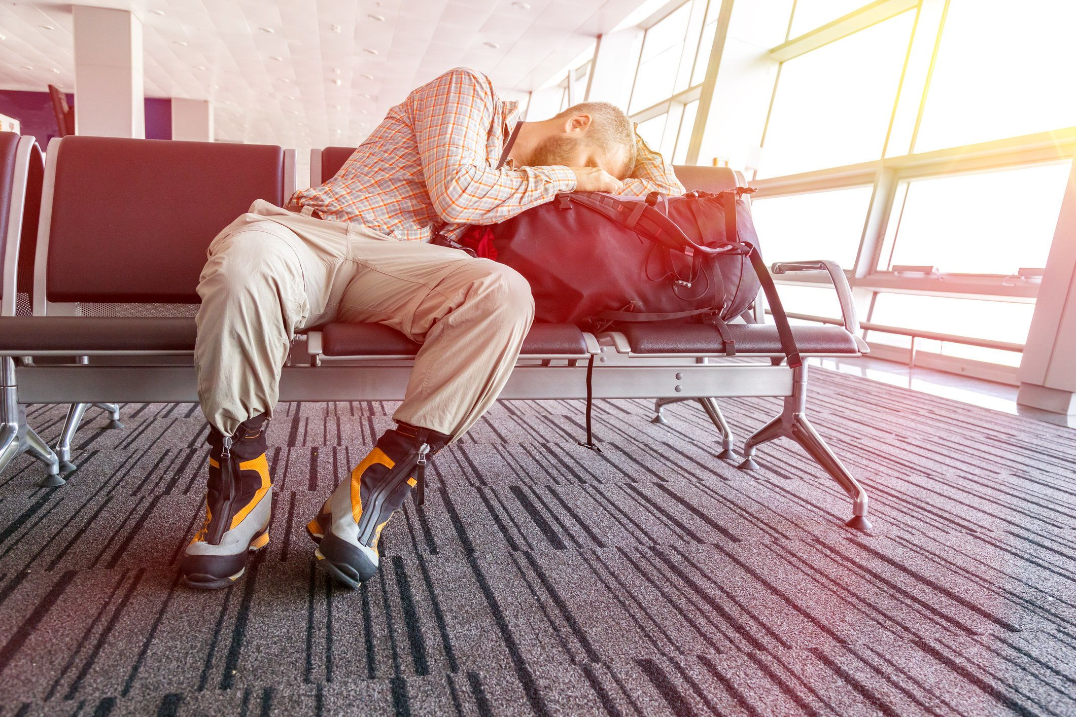 Man sleeping on his travel luggage inside airport terminal with back light bright sun coming throw window