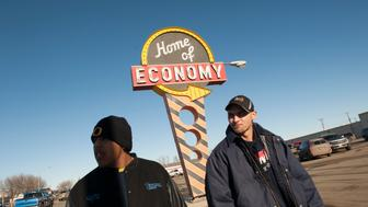 Bazileo Hernandez (L) and Jeff Williamson walk past a Home of Economy store along U.S. Route 85 while searching for jobs in Williston, North Dakota January 23, 2015. Home of Economy is a regional chain selling work clothing and boots to oilfield workers, among other things. Like so many before them, Terra Green, Jeff Williamson and Bazileo Hernandez came to North Dakota's oil country seeking a better life. They just came too late. Itinerant, unskilled workers could as recently as last spring show up in the No. 2 U.S. oil producing state and vie for salaries north of $100,000 per year with guaranteed housing. The steep drop in oil prices has changed that. After trying unsuccessfully for over a month to find work, the friends decided to leave Williston. REUTERS/Andrew Cullen   (UNITED STATES - Tags: BUSINESS COMMODITIES EMPLOYMENT SOCIETY TPX IMAGES OF THE DAY)   PICTURE 1 OF 28 FOR WIDER IMAGE STORY 'IN PURSUIT OF THE AMERICAN DREAM'  SEARCH 'CULLEN DREAM' FOR ALL IMAGES