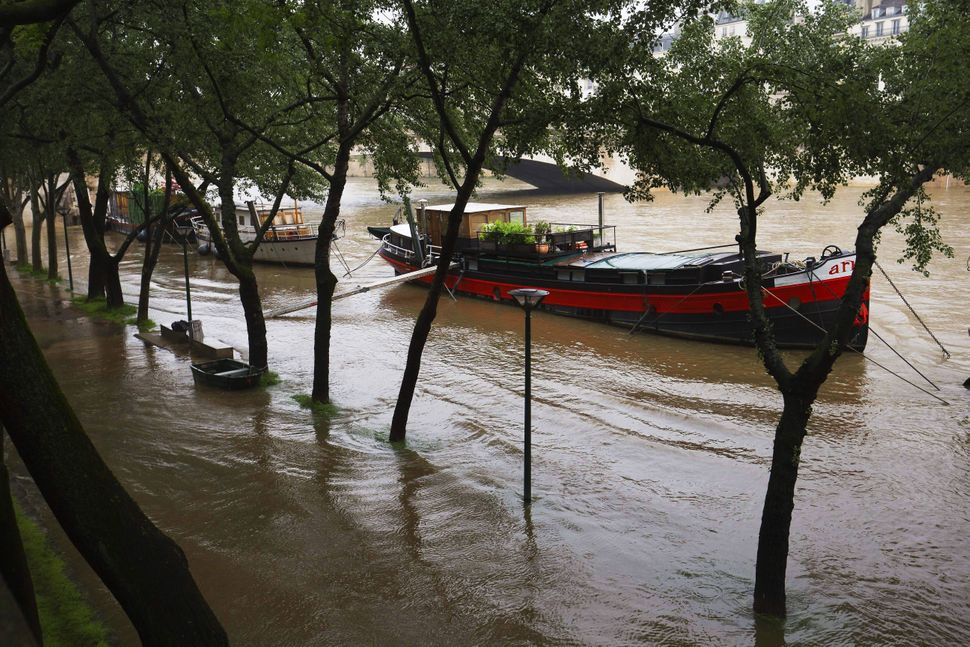 This photo shows a barge and a boat on the river Seine on Quai de la Tournelle after its banks became flooded following heavy