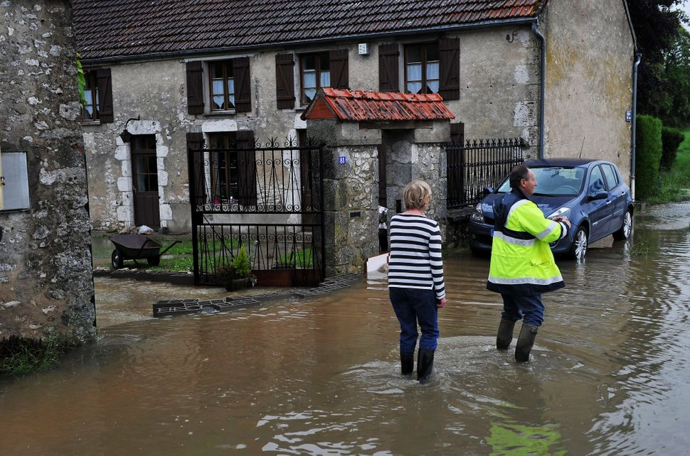 A woman stands next to her flooded house on May 31, 2016, in Meung-sur-Loire southern Orleans, following heaving rainfalls.