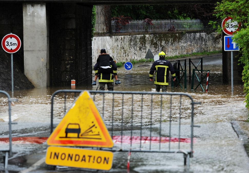 A fireman crosses a flooded road with a person on his back following heavy rainfalls on May 31, 2016, in Meung-sur-Loire sout