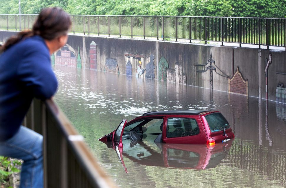 A man looks at a flooded car on a street on May 30, 2016, in Oberhausen after a heavy storm. At least four people died and se