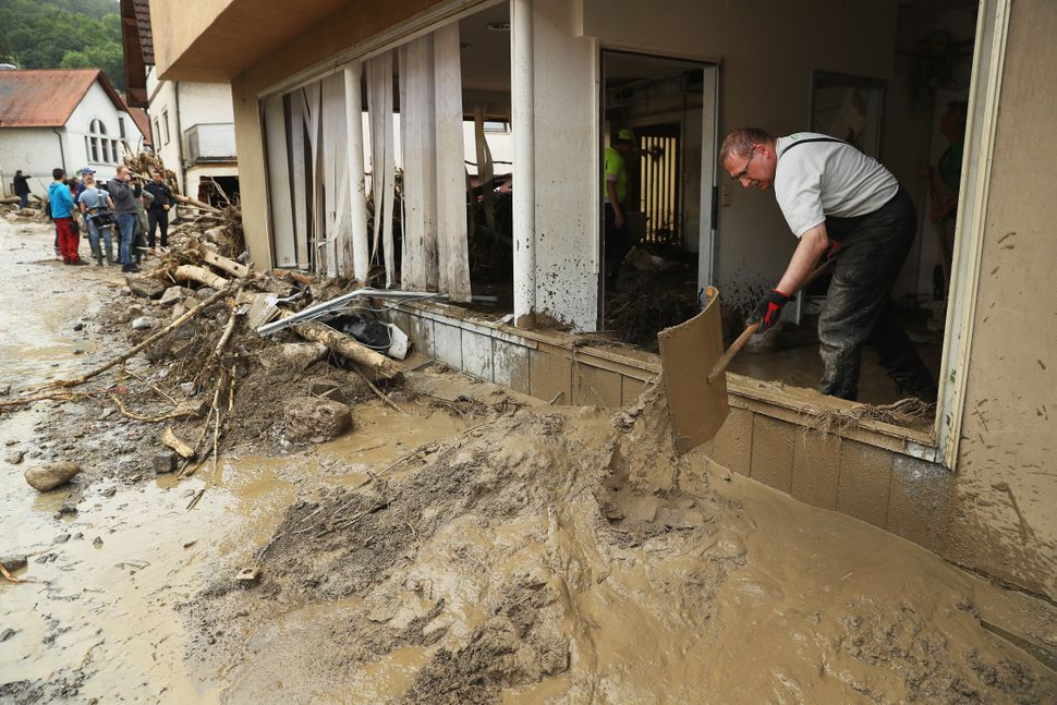 People clear mud from a flooded store in the village center following a furious flash flood the night before on May 30, 2016,