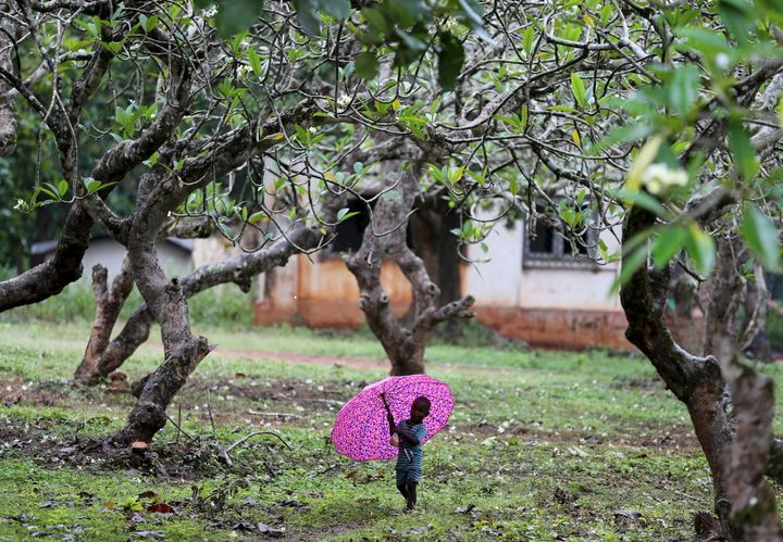 A boy who has been internally displaced walks with an umbrella in the rain in Bambari in October 2015. A fragile peace now pr