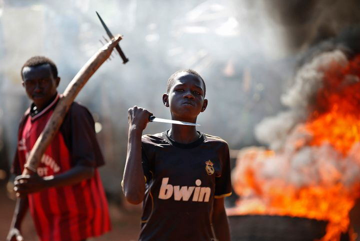 A boy gestures in front of a torched barricade during a protest in Bambari in May 2014.