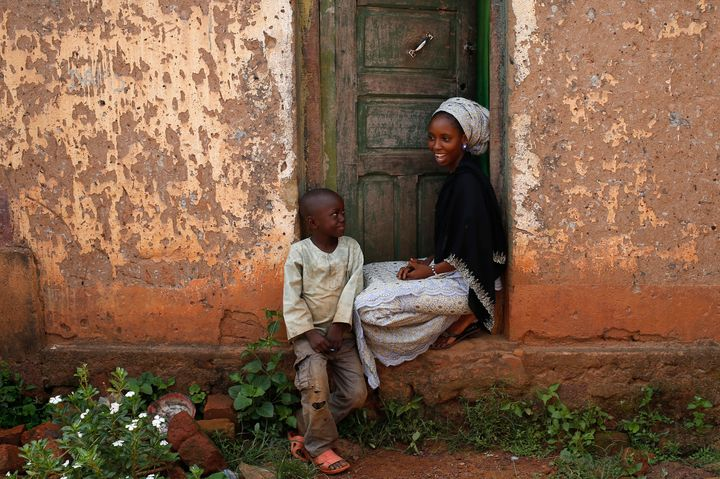 The future of the radio station in this fragile country remains precarious. Above, a woman and a boy sit outside their h