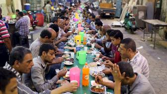 People eat their Iftar meal as they break their fast at charity tables that offer free food during the holy fasting month of Ramadan in Cairo, Egypt, June 23, 2015. REUTERS/Asmaa Waguih