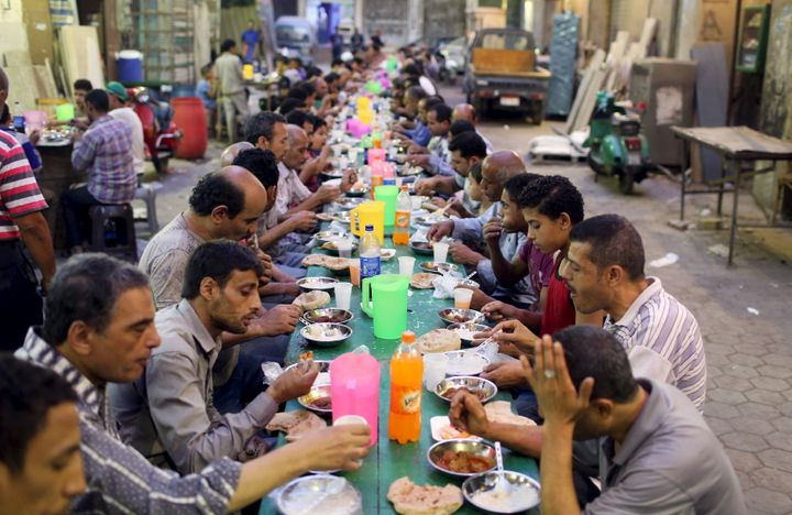 People eat their iftar meal as they break their fast at charity tables that offer free food during the holy fasting month of