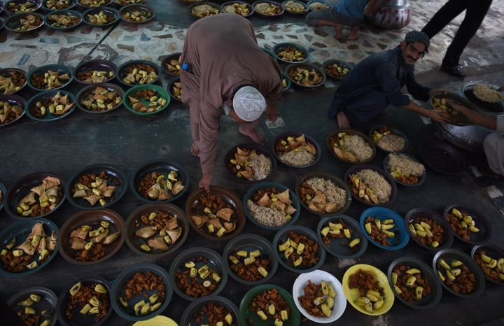 Pakistani volunteers prepare iftar food for devotees to break their Ramadan fast.