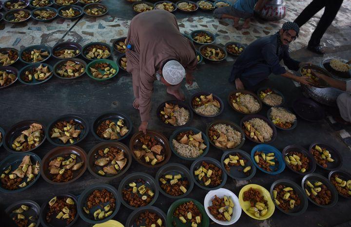 Pakistani volunteers prepare iftar food for devotees to break their Ramadan fast.