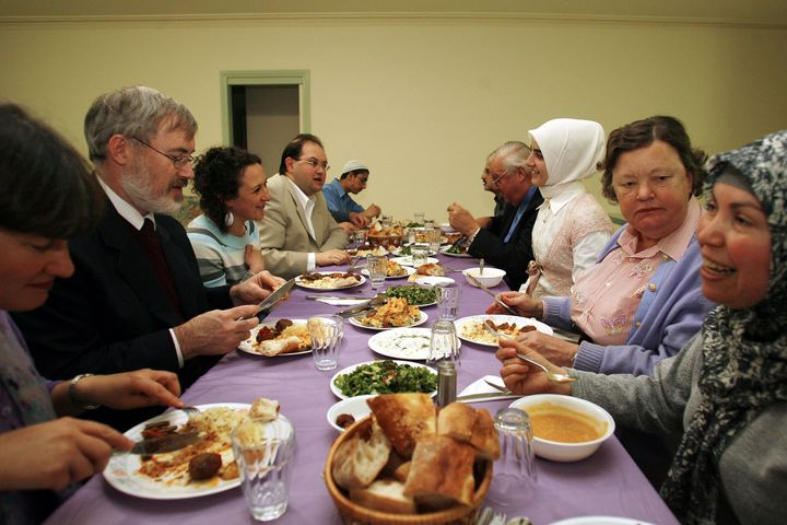 Members of several different religions participating in an interfaith meeting enjoy a traditional Turkish iftar dinner.