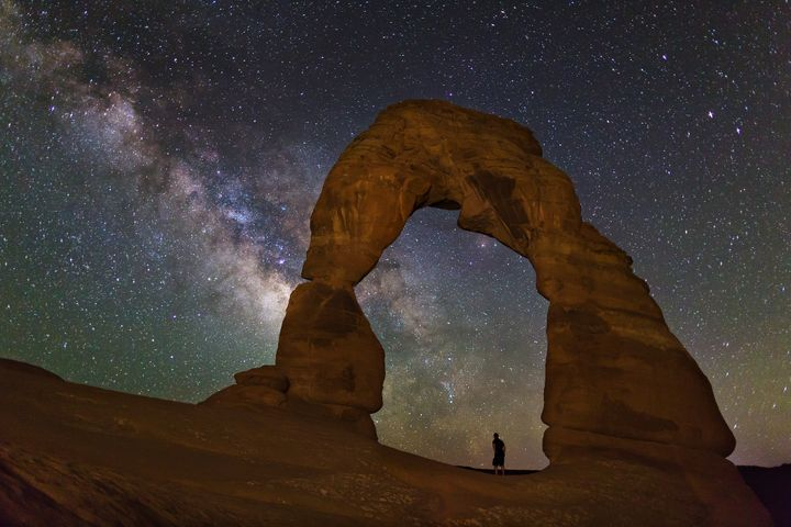 A person watches the Milky Way while standing insideUtah'sDelicate Arch.