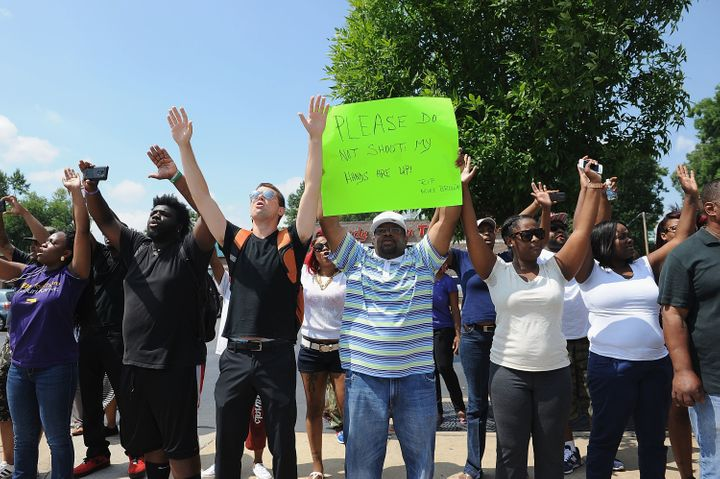 Protesters stand with arms in the air outside the Ferguson Police Department on Aug. 11, 2014.