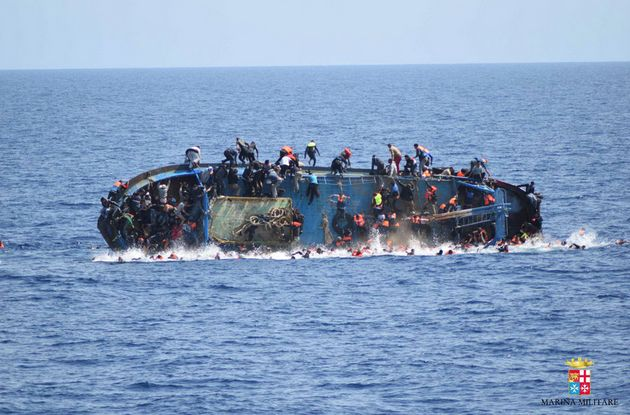 Desperate migrants cling to a capsized boat off the coast of