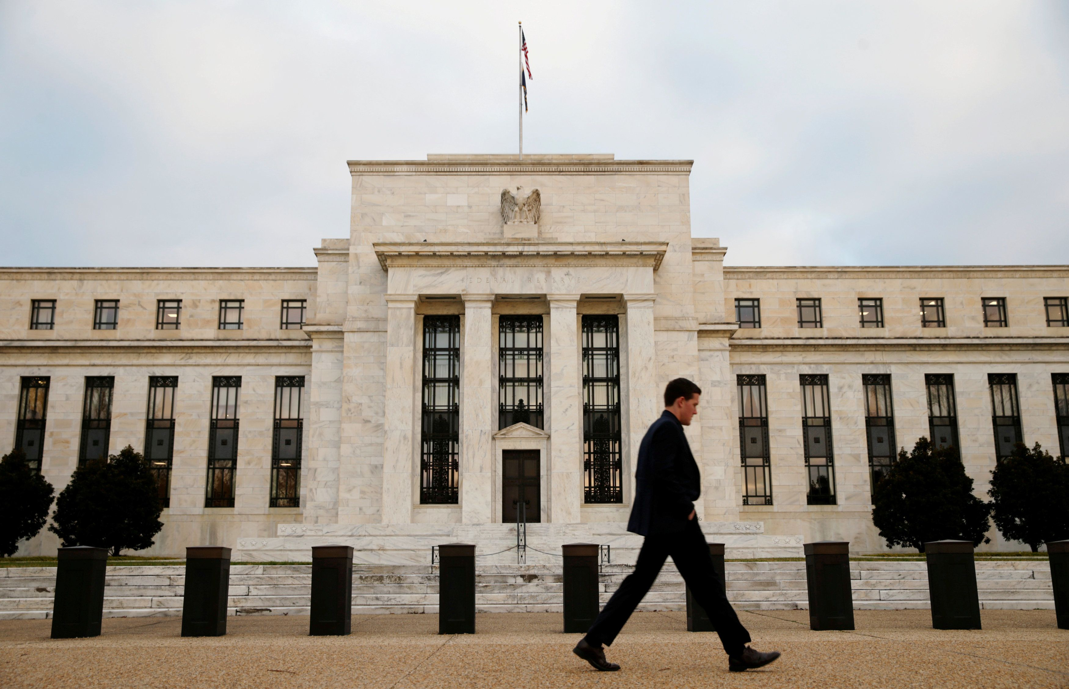 """A man walks past the Federal Reserve Bank in Washington, D.C., U.S. December 16, 2015. The Federal Reserve recorded more than 50 cyber breaches between 2011 and 2015, with several incidents described internally as """"espionage"""", according to records obtained by Reuters.  REUTERS/Kevin Lamarque/File Photo"""