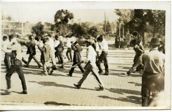 A digital scan of a postcard image of the Tulsa race riot shows blackprisoners being marched at gunpoint.