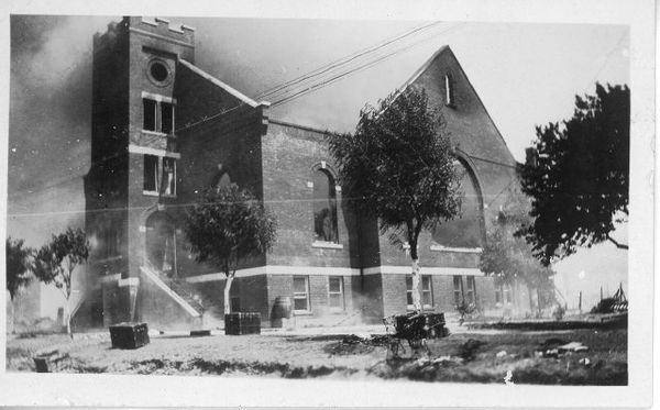 This image shows the Mt. Zion Baptist Church burning. The trunks and other items seen on the church lawn were placed there by