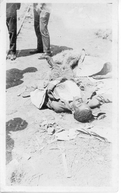 The body of a victim of the riot lays dead in the street.