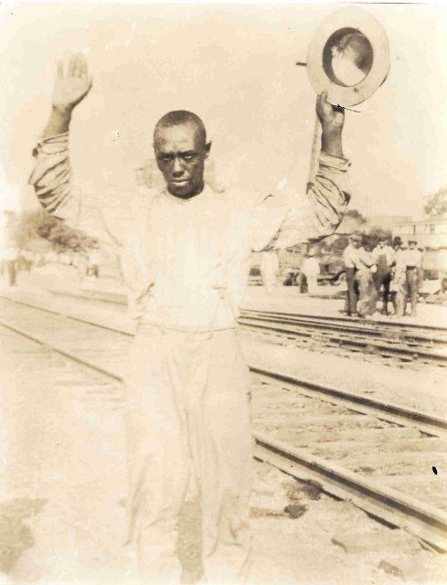 This photo shows a black man being detained during the Tulsa race riot while standing next to railroad tracks and holding his