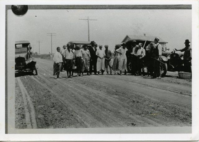 African-American detainees stand among armed whites after the Tulsa race riot.