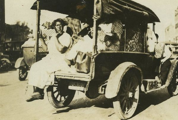 This photo shows a small truck loaded with people. A woman sits with her legs dangling from the back of the truck. An armed w